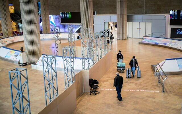 Passengers walk in the arrivals hall at the Ben Gurion International Airport on March 8, 2021 (Avshalom Sassoni/Flash90)