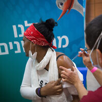 An Israeli receives a COVID-19 vaccine shot at a Leumit vaccination center in Tel Aviv, March 8, 2021. (Miriam Alster/Flash90)
