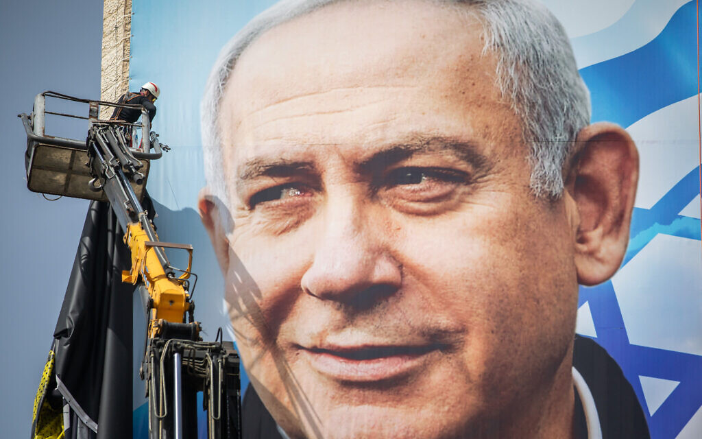 Israeli workers put up a giant election campaign poster showing Prime Minister Benjamin Netanyahu of the Likud party, in Jerusalem on March 10, 2021. (Yonatan Sindel/Flash90)