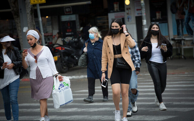 Israelis wear protective face masks as they walk in Tel Aviv on March 11, 2021. (Miriam Alster/FLASH90)