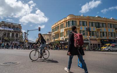 Illustrative: A woman bikes in Tel Aviv, on March 12, 2021.(Yahav Gamliel/Flash90)