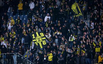 Soccer fans cheer during a match between Beitar Jerusalem FC and Ashdod FC at Teddy Kollek stadium in Jerusalem, on March 17, 2021. (Flash90)