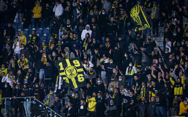 Soccer fans cheer during a match between Beitar Jerusalem FC and Ashdod FC at Teddy Kollek stadium in Jerusalem, on March 17, 2021. (Flash90)