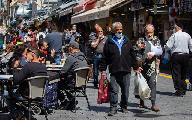 People shop and eat at the Mahane Yehuda Market on March 17, 2021 in Jerusalem (Olivier Fitoussi/Flash90)