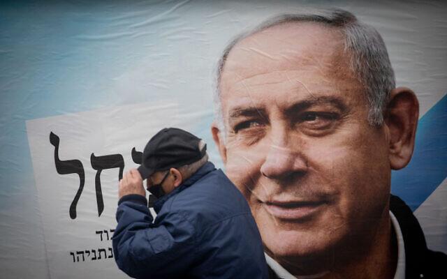 A man walks near an election campaign poster showing Prime Minister Benjamin Netanyahu in Jerusalem on March 18, 2021 (Yonatan Sindel/Flash90)