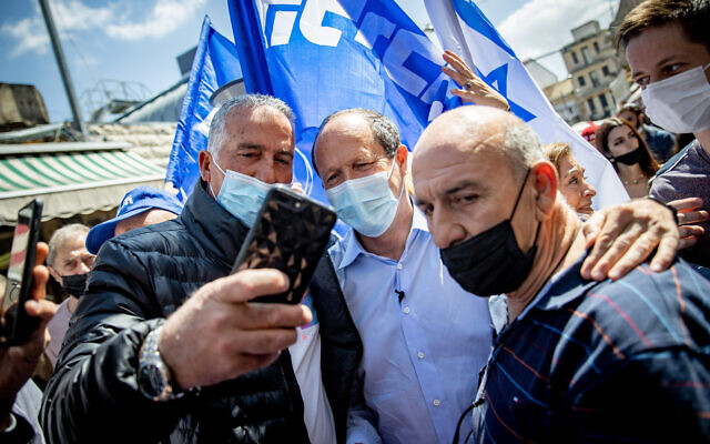 MK Nir Barkat, a lawmaker in Prime Minister Benjamin Netanyahu's Likud party, takes a selfie with supporters during a campaign stop at Jerusalem's Mahane Yehuda on March 19, 2021. (Yonatan Sindel/Flash90)