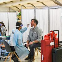 Medical technicians test passengers for COVID-19 at Ben Gurion International Airport near Tel Aviv on March 8, 2021. (Flash90)