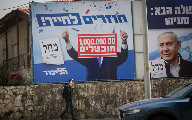 A ruined Likud campaign poster showing Benjamin Netanyahu's face covered by '1,000,000 unemployed' in Tel Aviv on March 21, 2021. (Miriam Alster/FLASH90)