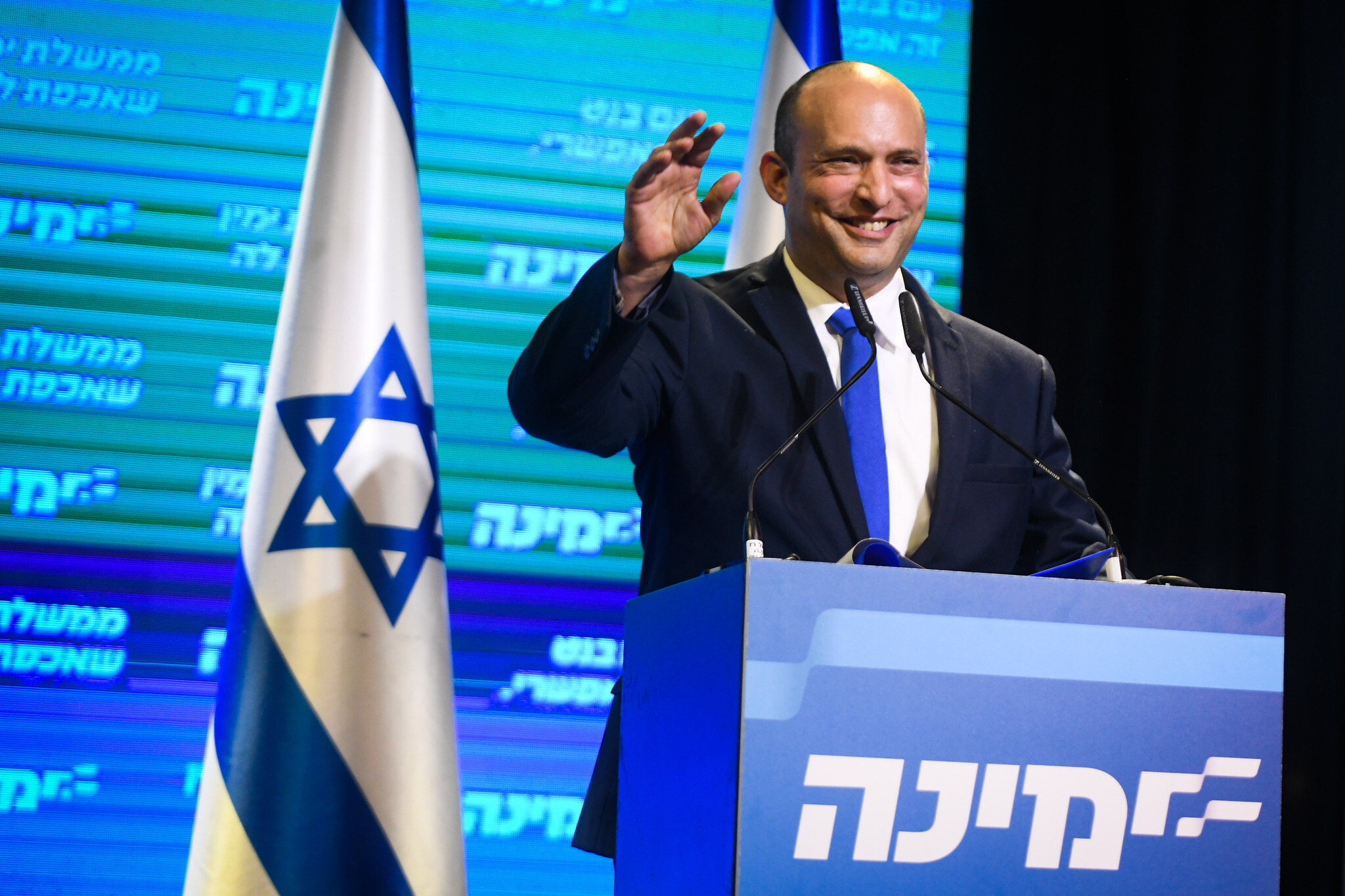 Naftali Bennett, head of the Yamina party seen with Yamina supporters at the party headquarters in Petah Tikva, on election night, on March 23, 2021. (Avi Dishi/Flash90)