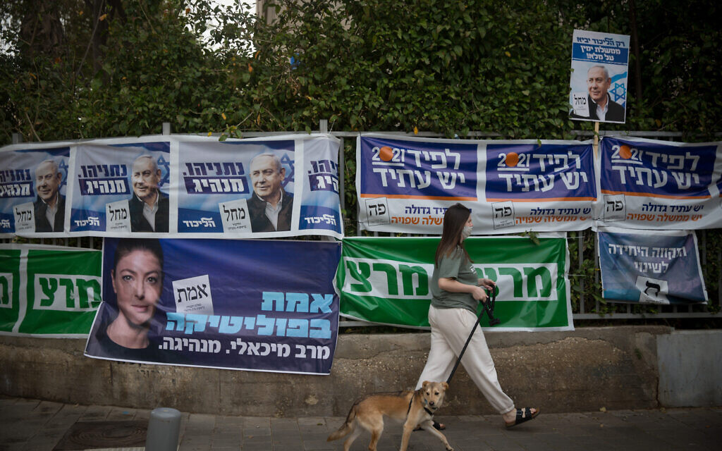 A woman walks past campaign posters in Tel Aviv on March 23, 2021. (Miriam Alster/Flash90)