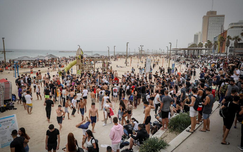 Israelis enjoy the hot, dusty election day weather at the beach in Tel Aviv on March 23, 2021. (Noam Revkin Fenton/Flash90)