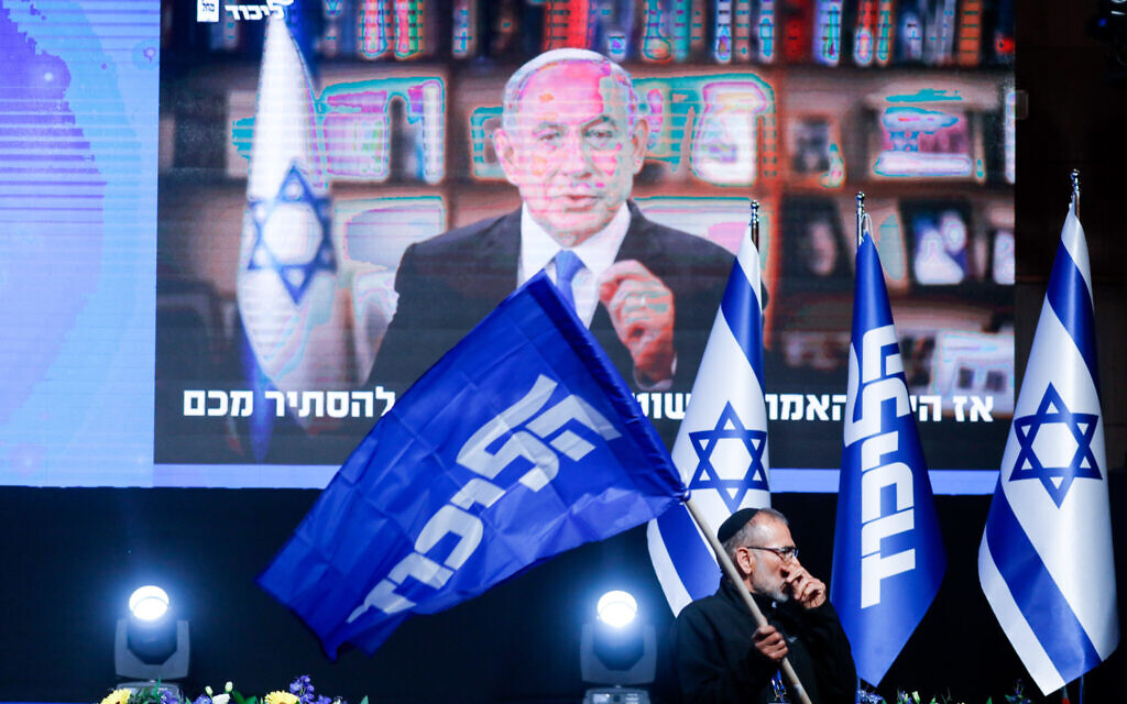 A Likud supporter in front of a video of Benjamin Netanyahu at a party event in Jerusalem on March 23, 2021. (Olivier Fitoussi/Flash90)