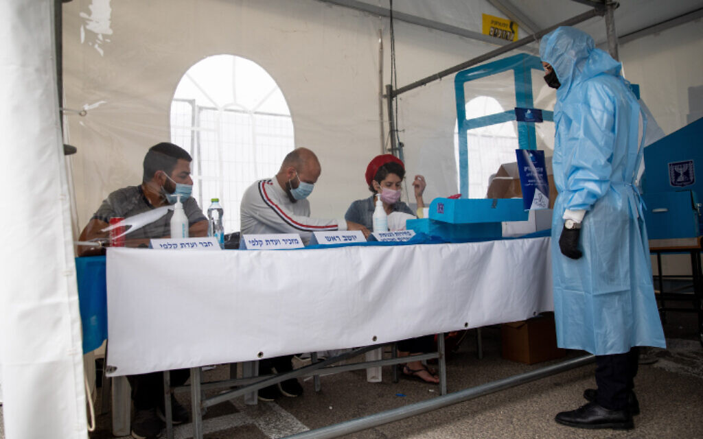 Israeli electoral workers at a polling station for COVID-19 carriers in Jerusalem on March 23, 2021. (Shir Torem/Flash90)