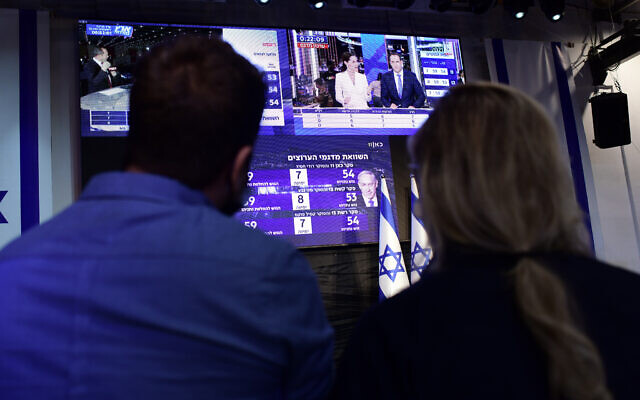 Activists in Tel Aviv watch the exit polls on elections night, on March 23, 2021. (Tomer Neuberg/Flash90)