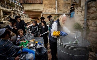 Ultra-Orthodox Jews dip cooking pots to rid any traces of leavening in preparation for the upcoming Passover holiday, in the ultra orthodox neighborhood of Mea Shearim in Jerusalem on March 25, 2021 (Yonatan Sindel/Flash90)
