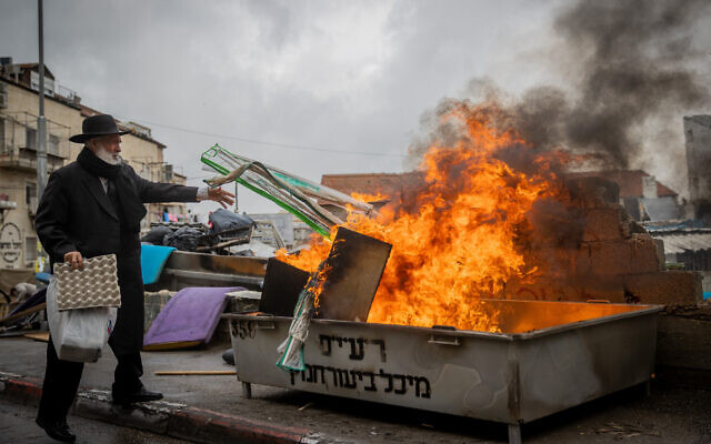 Ultra-Orthodox Jews burn leavened items in a final preparation before the Passover holiday in the Mea Shearim neighborhood of Jerusalem, March 26, 2021 (Yonatan Sindel/Flash90)