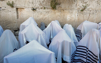 Jewish worshippers cover themselves with prayer shawls as they pray in front of the Western Wall, during the priestly blessing event of the Passover holiday, March 29, 2021. (Olivier Fitoussi/Flash90)