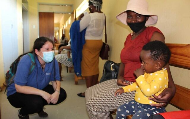 A member of the nonprofit IsraAID (left) speaks to residents of Eswatini at a hospital in the south African country (courtesy)