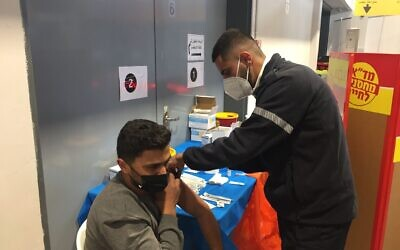 Ahmad Atwan, a Palestinian from a town near Hebron, receives the first dose of a coronavirus vaccine by Magen David Adom during an Israeli campaign to immunize Palestinians who work in Israel (Aaron Boxerman/The Times of Israel)