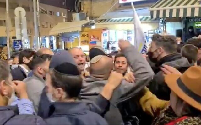 Screen capture from video of a clash between Likud party activits and New Hope party Knesset candidate Ofer Berkovitch as he campaigned in Jerusalem's Mahane Yehudah market, March 15, 2021. (Twitter)