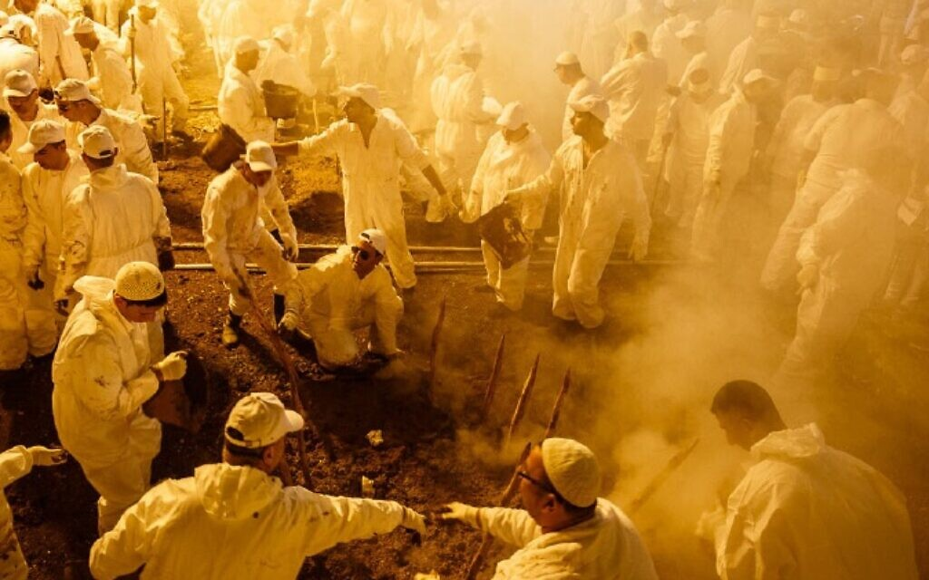 Samaritan men at Passover lamb cooking pits on Mt. Gerizim, Palestinian territories, April 2016. (Yadid Levy)