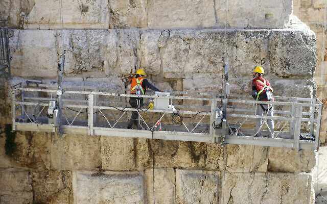 Two workers help conserve Phasael tower as part of renewal project in Tower of David complex. (Ricky Rachman/ Tower of David Museum)