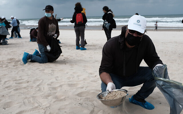 Israelis clean tar off the Bat Yam beach following an offshore oil spill which polluted most of the Israeli coastline, March 2, 2021. (Tomer Neuberg/Flash90)