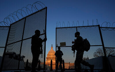 US National Guard soldiers open a gate of the razor wire-topped perimeter fence around the Capitol building in Washington, March 8, 2021. (AP Photo/Carolyn Kaster)