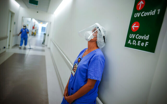 A health worker pauses in the ICU unit for COVID-19 patients at the Hospital das Clinicas in Porto Alegre, Brazil, March 19, 2021. (AP Photo/Jefferson Bernardes)