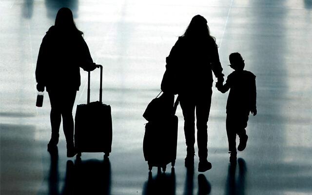 Travelers walk in Salt Lake City International Airport, in Salt Lake City, Utah, March 9, 2021. (AP Photo/Rick Bowmer)