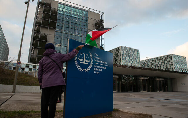 A demonstrators poses with a Palestinian flag outside the International Criminal Court (ICC) during a rally urging the court to prosecute Israel for alleged war crimes in The Hague, Netherlands, Nov. 29, 2019. (AP Photo/Peter Dejong)