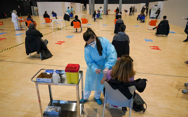 "Health workers administer doses of the AstraZeneca vaccine against COVID-19 inside the convention center known as ""La Nuvola"", The Cloud, in Rome, Italy, March 10, 2021. (AP Photo/Andrew Medichini)"
