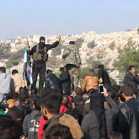 Illustrative: Hayat Tahrir al-Sham jihadists try to disperse people who gathered at the Bab al-Hawa border gate with Turkey to protest bombing by the Syrian regime, Dec. 20, 2019. (AP Photo/APTN)