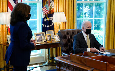 US Vice President Kamala Harris listens as President Joe Biden speaks after signing the PPP Extension Act of 2021, in the Oval Office of the White House in Washington, March 30, 2021. (AP Photo/Evan Vucci)