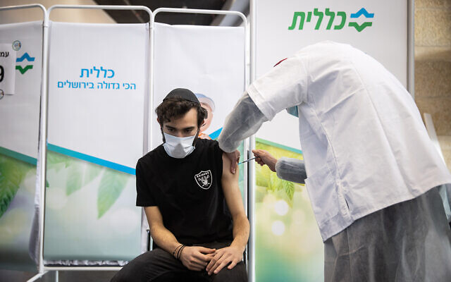 An Israeli receives a COVID-19 vaccine, at Clalit vaccination center in Jerusalem, on March 8, 2021. (Yonatan Sindel/Flash90)