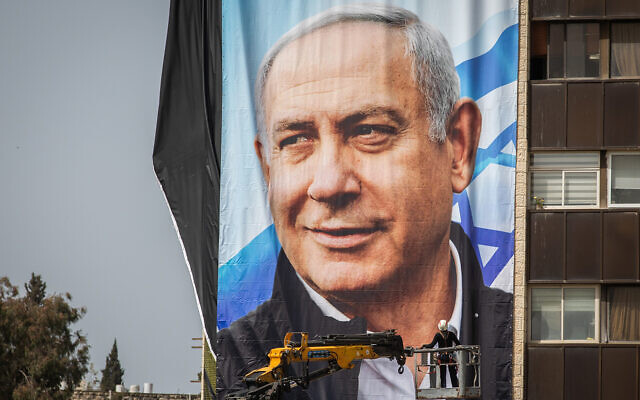 Israeli workers hang large election campaign posters of the Likud party, as part of the Likud election campaign, in Jerusalem on March 10, 2021. (Yonatan Sindel/Flash90)