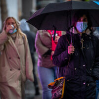 People wearing face masks take cover from rain as they walk on Jaffa Street in the city center of Jerusalem, on March 4, 2021. (Olivier Fitoussi/Flash90)