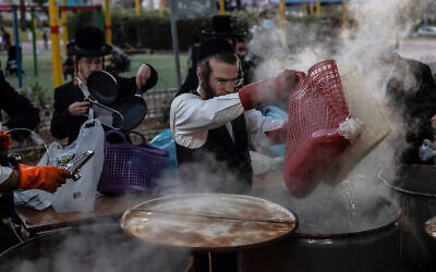 An ultra-Orthodox man dips cooking utensils in boiling water to remove remains of leaven in preparation for the upcoming holiday of Passover in Ashdod, March 25, 2021. (AP Photo/Tsafrir Abayov)