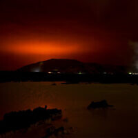 The red shimmer from magma flowing out from the erupting Fagradalsfjall volcano behind the landmark Blue Lagoon, some 45 km west of the Icelandic capital Reykjavik, on March 19, 2021. (Halldor KOLBEINS / AFP)