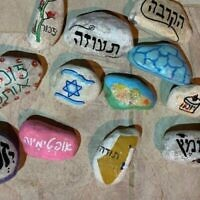 Pebbles with personal messages from bereaved families as part of the Navah organization's 'Stones with a person's heart' project. (Courtesy: Navah)
