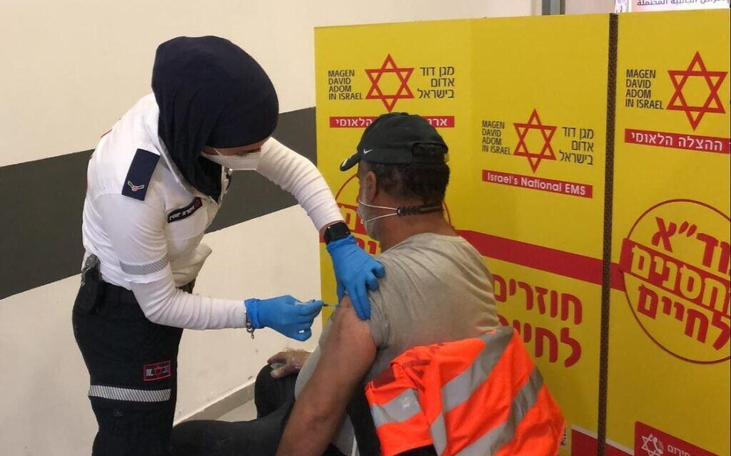 A Palestinian worker gets vaccinated by Israeli Magen David Adom staff at the Sha'ar Efraim checkpoint in the West Bank, March 4, 2021 (COGAT)