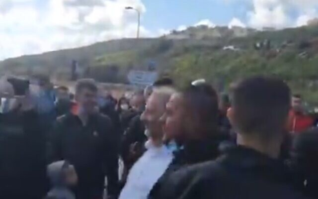 MK Mansour Abbas (c) is led away by security guards after being heckled and accosted at a protest in Umm el-Fahm on March 5, 2021.(Screencapture/Twitter)