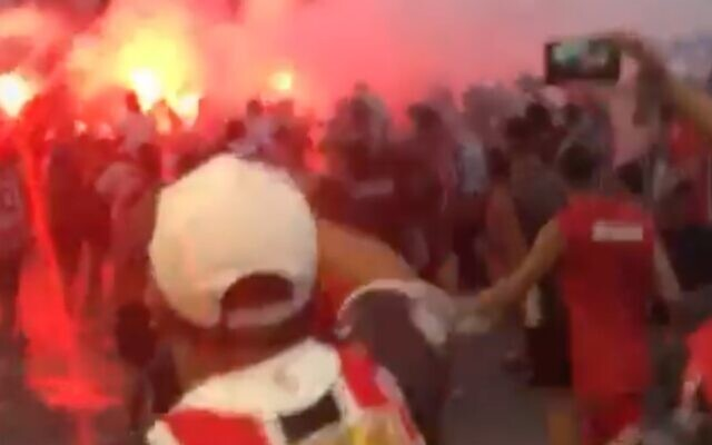 A screenshot from the viral video of Chacarita fans chanting an anti-Semitic line shows them marching near a bonfire on the street. (via JTA)