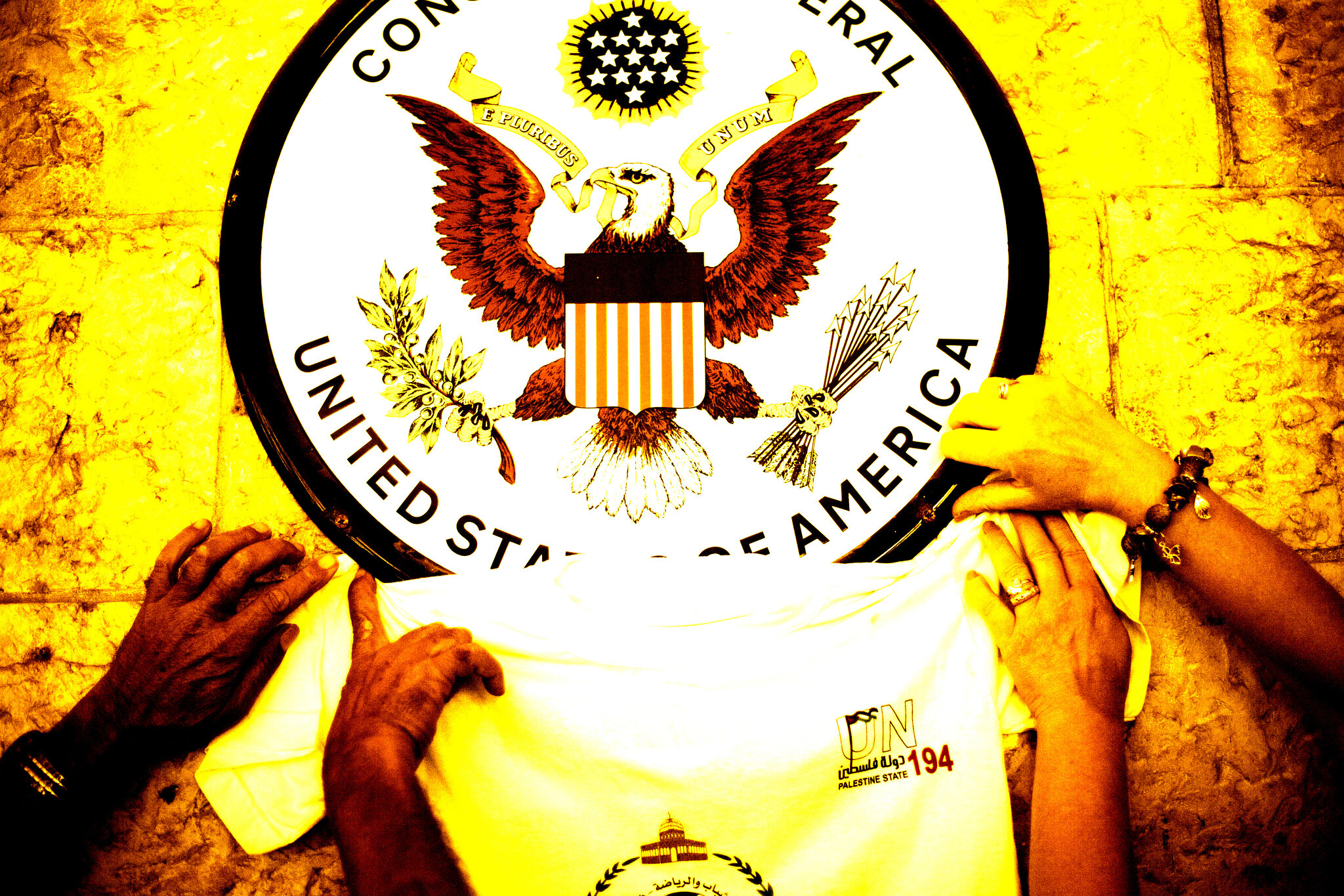 Illustration using a photo of Palestinian activists placing a T-shirt with a logo representing their statehood bid underneath the US Consulate sign during a rally on September 21, 2011, in  Jerusalem.  (AP/Dusan Vranic; Illustration: Joshua Davidovich)