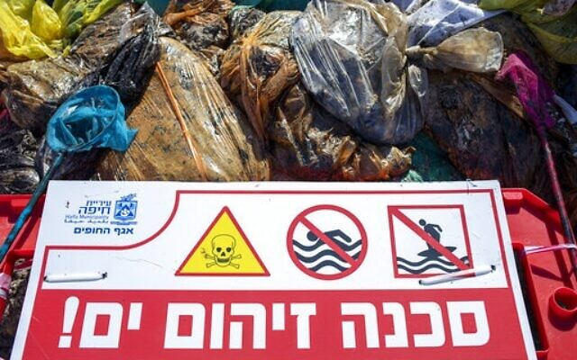 "A sign that reads, ""Danger, polluted sea"" is placed on Haifa beach, northern Israel, next to bags full of tar collected by volunteers following an oil spill in the Mediterranean Sea, February 28, 2021. (AP Photo/Ariel Schalit)"