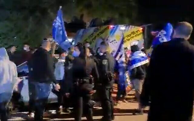 Supporters of Prime Minister Benjamin Netanyahu are watched by police officers outside an event for Gideon Sa'ar's New Hope party, March 13, 2020 Screen grab/Channel 13)