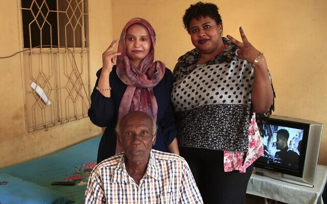 Amin Israil (bottom), the grandson of an Iraqi Jew who settled in Sudan and whose family later converted to Islam, his daughter Salma (L), and Yosar Basha (R), another Sudanese woman descended of Jewish origins, pose for a photo together at Israil's home during an interview with AFP in Wad Madani, the capital of Sudan's east-central al-Jazirah state, on February 11, 2021. - The Jewish community in Sudan was one of the smallest in the Middle East, but it, like those of other Arab states, dwindled in the latter half of the 20th century, as tensions surrounding the 1948 creation of Israel permeated the region. Like elsewhere in the Arab world, Sudanese Jews bore the brunt of growing anti-Israel sentiment amid conflict with the Jewish state. Decades later, their descendants see a recent rapprochement between their country and Israel as an opportunity to connect with their origins. (Photo by Ebrahim HAMID / AFP)