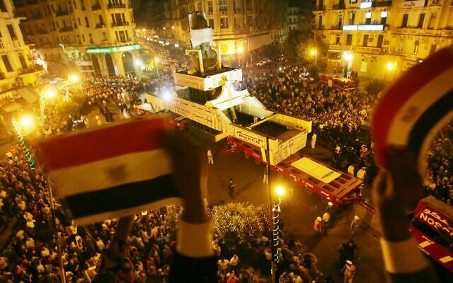 In this file photo taken on August 25, 2006, Egyptians wave their national flag from a balcony as they bid farewell to the Ramses II colossal statue at Talat Harb Square, as it's moved from the polluted capital city Cairo to a spot near the Pyramids in Giza, closer to its original site (Khaled DESOUKI / AFP)