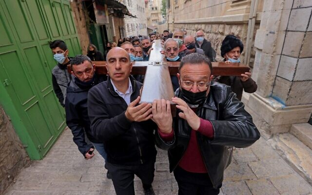 Christian worshippers carry a wooden cross along the Via Dolorosa (Way of Suffering) in Jerusalem's Old City during the Good Friday procession on April 2, 2021. (Photo by Emmanuel DUNAND / AFP)