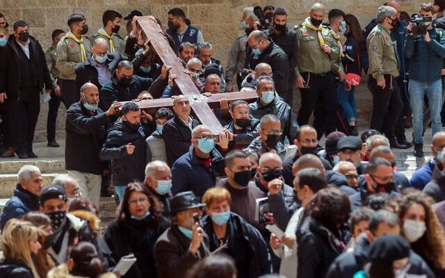 Christian worshippers carrying a wooden cross arrive at the Church of the Holy Sepulchre, during a Good Friday procession along the Via Dolorosa (Way of Suffering) in Jerusalem's Old City on April 2, 2021. (Emmanuel DUNAND / AFP)